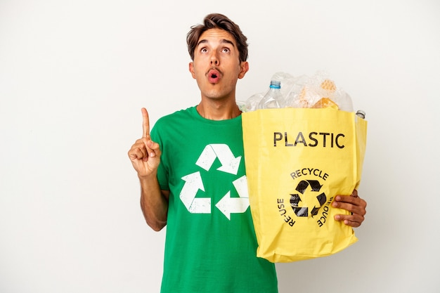 Young mixed race man recycling plastic isolated on yellow background pointing upside with opened mouth.
