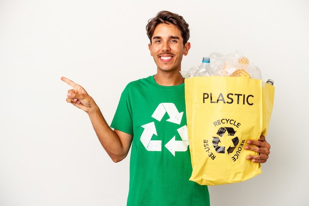 Young mixed race man recycling plastic isolated on yellow background smiling and pointing aside, showing something at blank space.