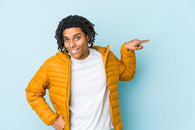 若い混血男が離れて人差し指で元気に指している笑顔。