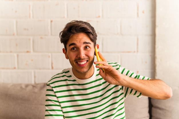 彼のソファで電話で話している若い混血の男