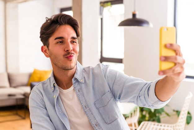 Young mixed race man talking on the phone in a kitchen