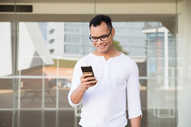 Young mixed-race man texting on phone, smiling. front view