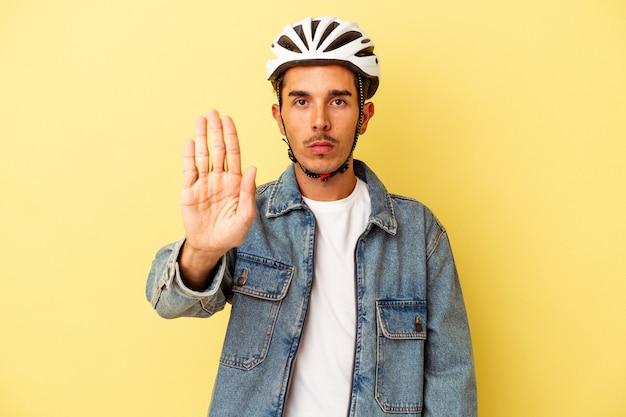 노란색 배경에 격리된 헬멧 자전거를 입은 젊은 혼혈 남성이 정지 신호를 보여주며 손을 뻗은 채 서 있습니다.