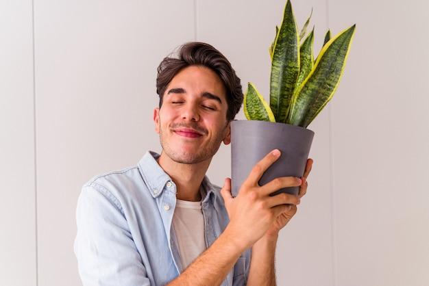 부엌에서 식물을 가진 젊은 혼혈 남자