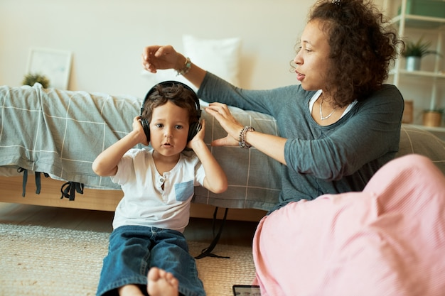 Young mixed race mother babysitting her toddler son who is sitting on floor in wireless headphones