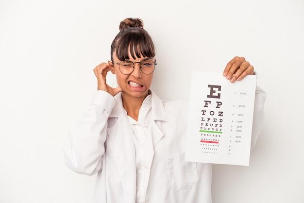 手で耳を覆う白い背景で隔離のテストを行う若い混血眼鏡技師の女性。