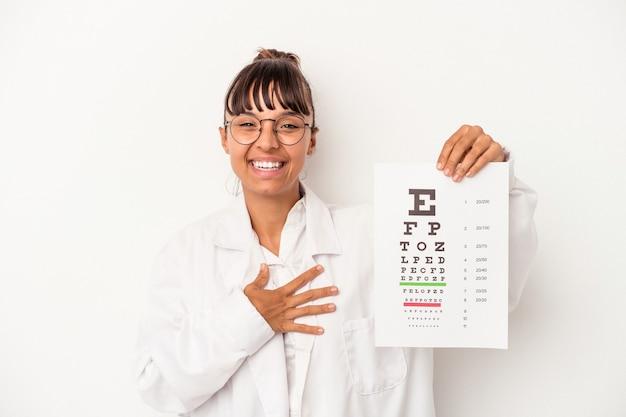 Молодая женщина-оптик смешанной расы делает тест, изолированные на белом фоне, смеясь и весело.