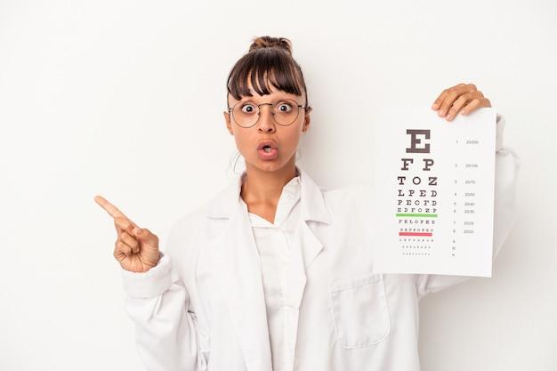 Молодая женщина-оптик смешанной расы делает тест на белом фоне, указывая в сторону