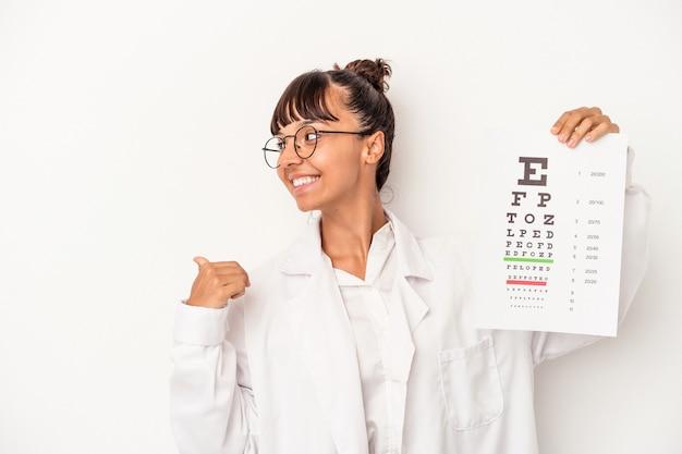 Молодая женщина-оптик смешанной расы делает тест, изолированный на белом фоне, указывает пальцем далеко, смеясь и беззаботно.