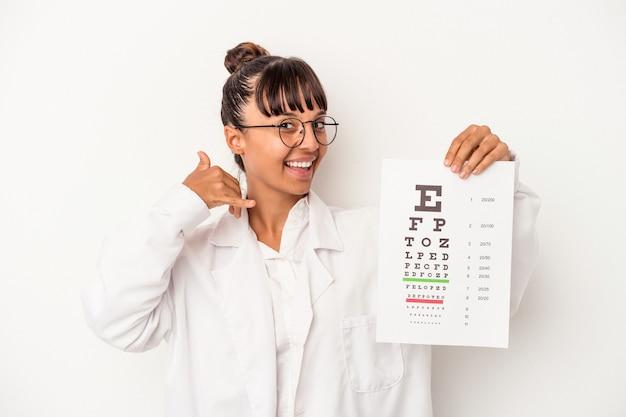 Молодая женщина-оптик смешанной расы делает тест, изолированный на белом фоне, показывая жест звонка по мобильному телефону с пальцами.