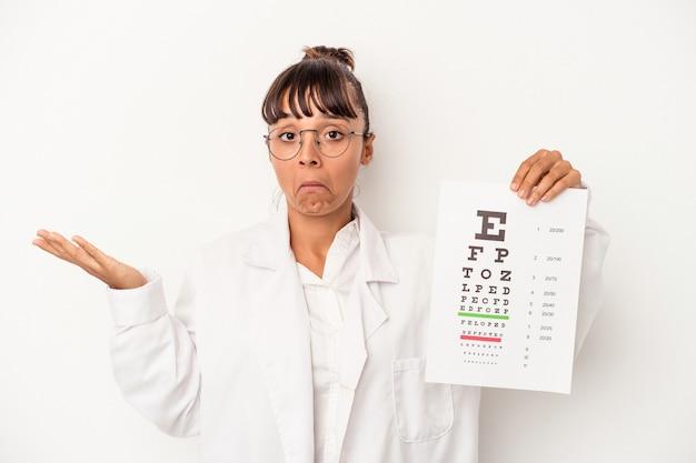 흰색 배경에 격리된 테스트를 하는 젊은 혼혈 안경점 여성은 어깨를 으쓱하고 혼란스러운 눈을 뜨고 있습니다.