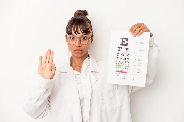 一時停止の標識を示して、あなたを防ぐために伸ばした手で立っている白い背景で隔離のテストをしている若い混血眼鏡技師の女性。