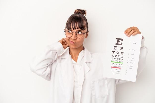 頭の後ろに触れて、考えて、選択をする白い背景で隔離のテストをしている若い混血眼鏡技師の女性。
