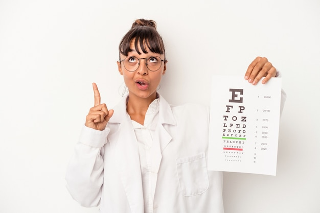 Young mixed race optician woman doing a test isolated on white background  pointing upside with opened mouth.