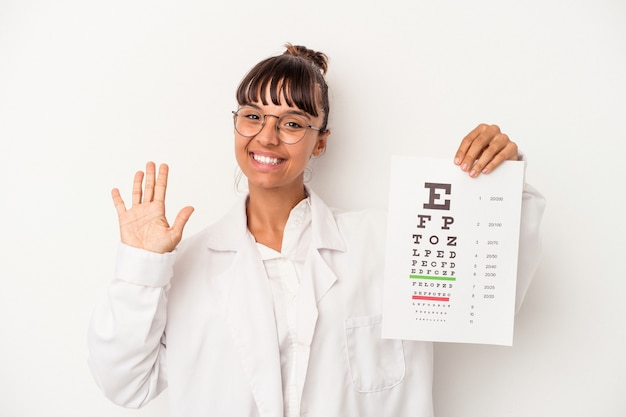 Young mixed race optician woman doing a test isolated on white background  smiling cheerful showing number five with fingers.