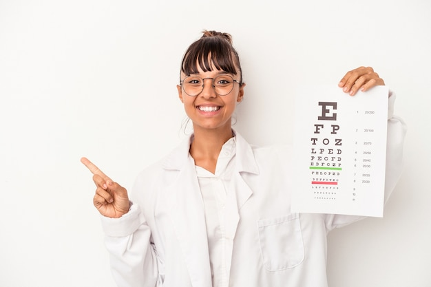 Young mixed race optician woman doing a test isolated on white background  smiling and pointing aside, showing something at blank space.