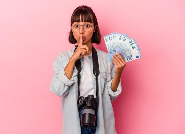 Молодая женщина-фотограф смешанной расы, держащая счета, изолированные на розовом фоне, хранящая в секрете или просящая молчания.