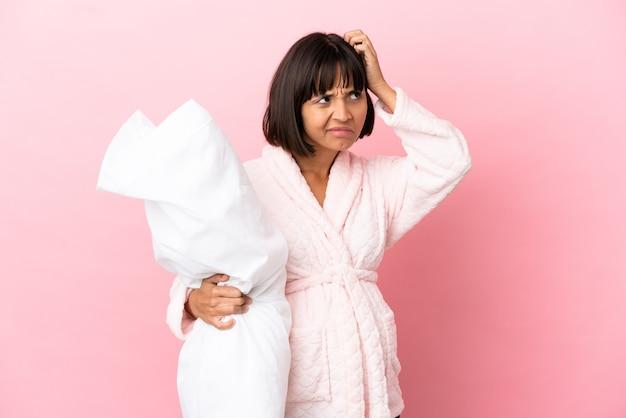 Молодая беременная женщина смешанной расы изолирована на розовом фоне в пижаме и сомневается с запутанным выражением лица
