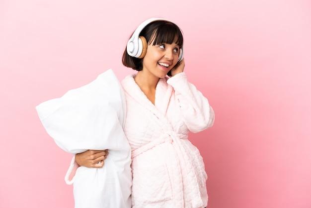 パジャマと枕を保持し、音楽を聴いてピンクの背景に分離された若い混血妊婦
