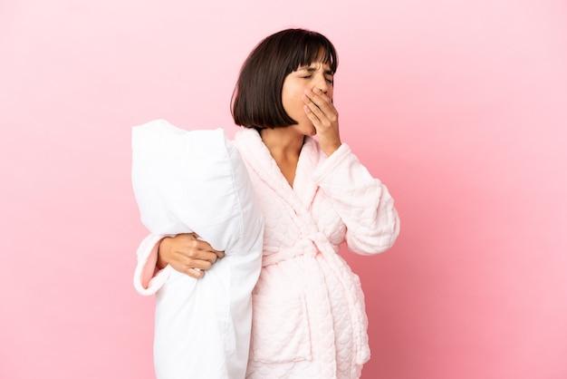Молодая беременная женщина смешанной расы изолирована на розовом фоне в пижаме и держит подушку и зевает