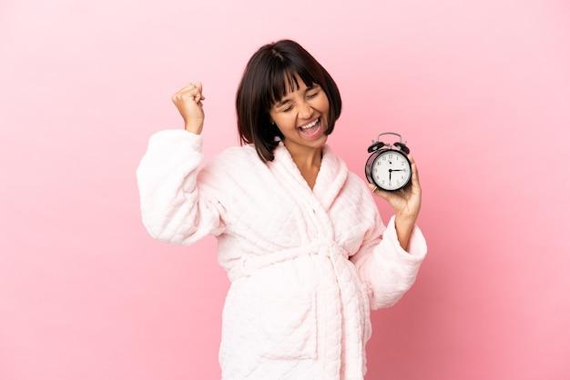 Молодая беременная женщина смешанной расы изолирована на розовом фоне в пижаме и держит часы, делая жест победы
