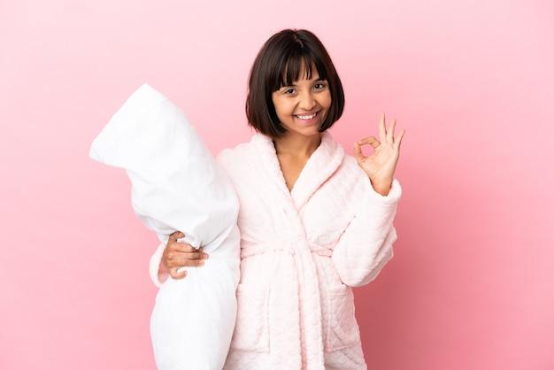 Молодая беременная женщина смешанной расы изолирована на розовом фоне в пижаме и показывает пальцами знак ок
