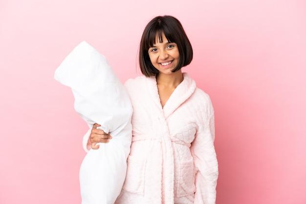 パジャマと笑顔でピンクの背景に分離された若い混血妊婦