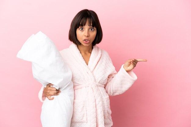 Молодая беременная женщина смешанной расы изолирована на розовом фоне в пижаме и удивлена, указывая сторону