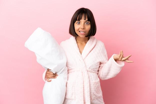 Молодая беременная женщина смешанной расы изолирована на розовом фоне в пижаме и с шокированным выражением лица