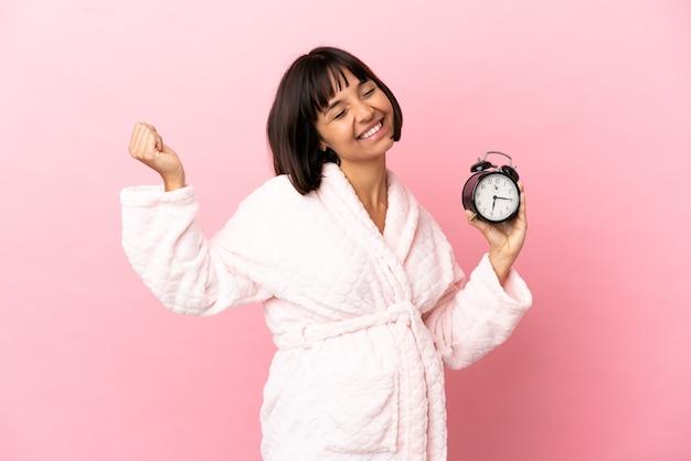 Молодая беременная женщина смешанной расы изолирована на розовой поверхности в пижаме и держит часы со счастливым выражением лица