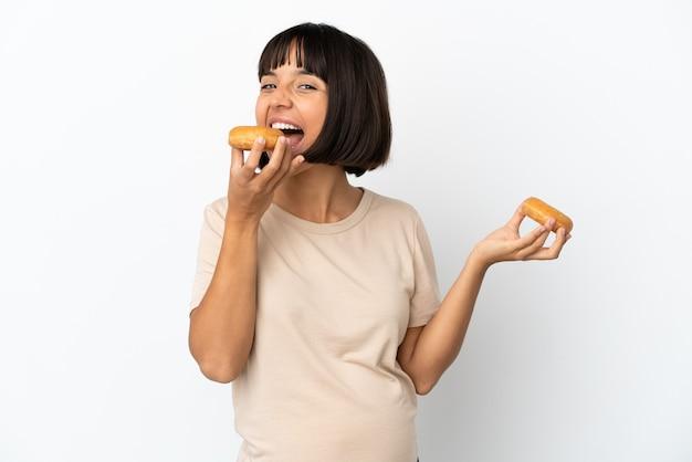 Молодая беременная женщина смешанной расы, изолированные на белом фоне, ест пончик