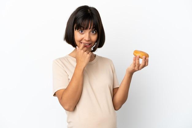 Молодая беременная женщина смешанной расы, изолированные на белом фоне, держа пончик