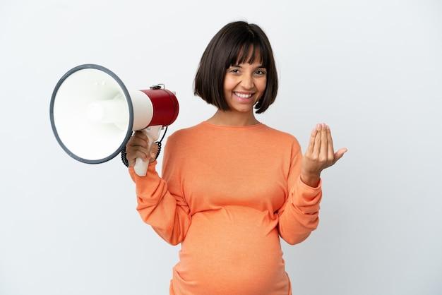 Молодая беременная женщина смешанной расы, изолированная на белом фоне, держит мегафон и приглашает прийти с рукой
