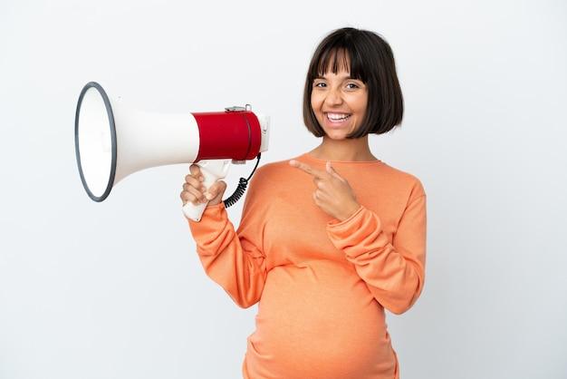 Молодая беременная женщина смешанной расы изолирована на белом фоне, держа мегафон и указывая сторону