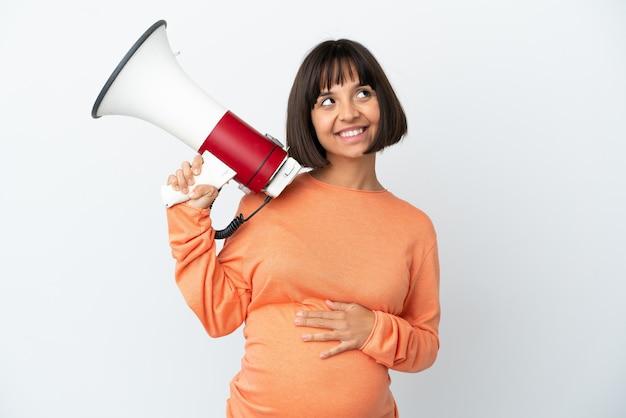 Молодая беременная женщина смешанной расы изолирована на белом фоне, держа мегафон и думая