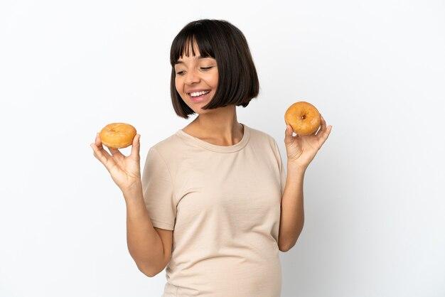 幸せな表情でドーナツを保持している白い背景で隔離の若い混血妊婦