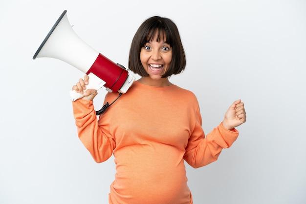 Молодая беременная женщина смешанной расы, изолированная на белом фоне, кричит в мегафон и указывает сторону