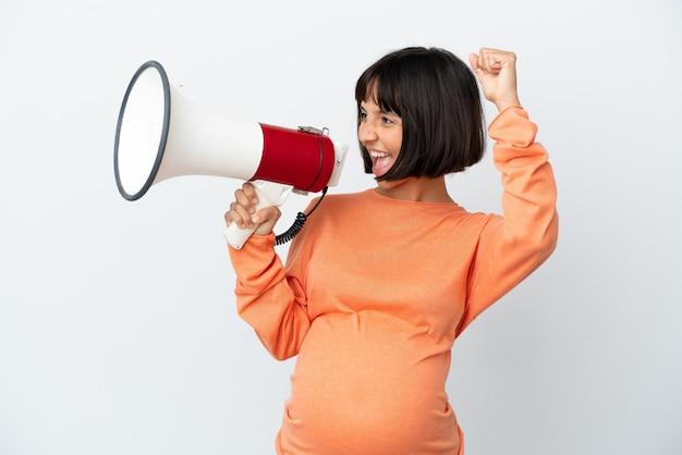Молодая беременная женщина смешанной расы, изолированная на белом фоне, кричит в мегафон, чтобы объявить что-то в боковом положении