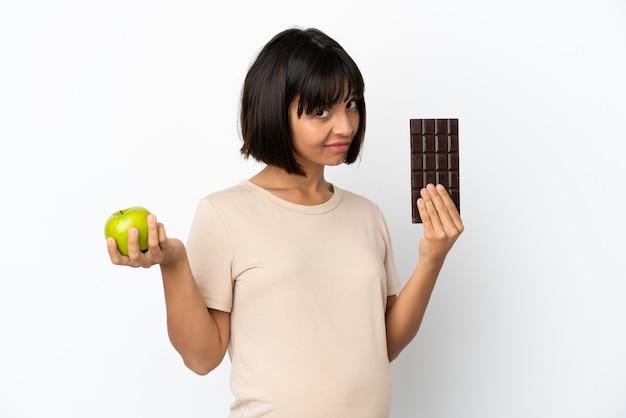 片方の手にチョコレートタブレット、もう片方の手にリンゴを取る白い背景で隔離の若い混血妊婦