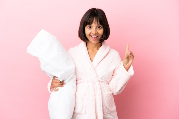 Young mixed race pregnant woman isolated on pink background in pajamas and pointing up a great idea