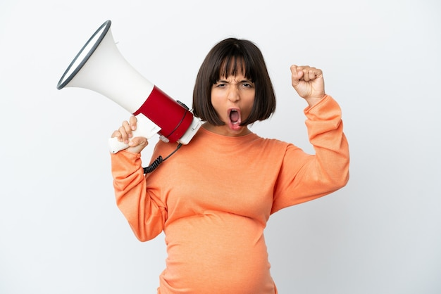 Young mixed race pregnant woman isolated on white background shouting through a megaphone to announce something