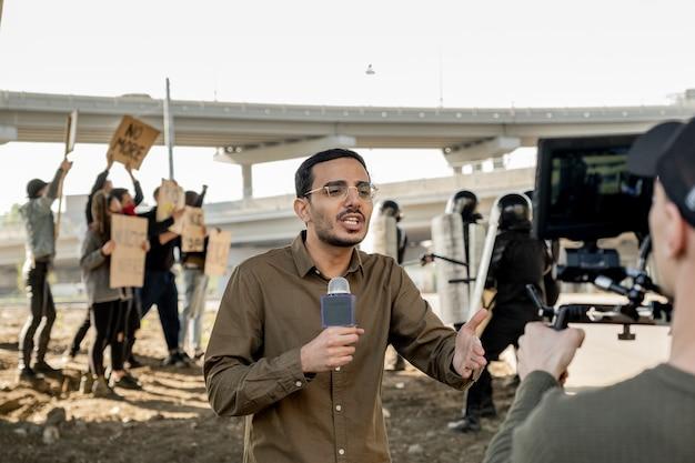 Молодой репортер смешанной расы с бородой использует микрофон во время освещения беспорядков в городе: омон сдерживает толпу протестующих