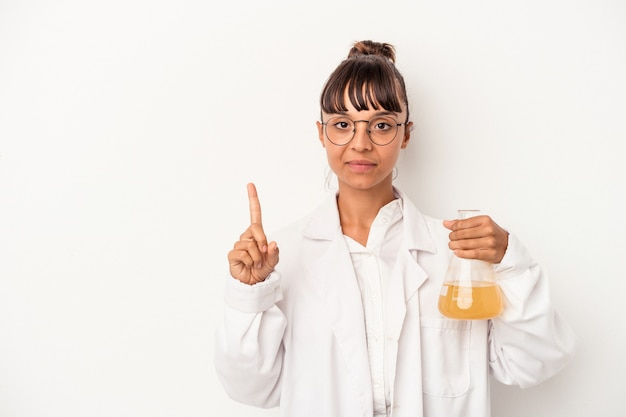 Young mixed race scientist woman holding a test tube isolated on white background  showing number one with finger.