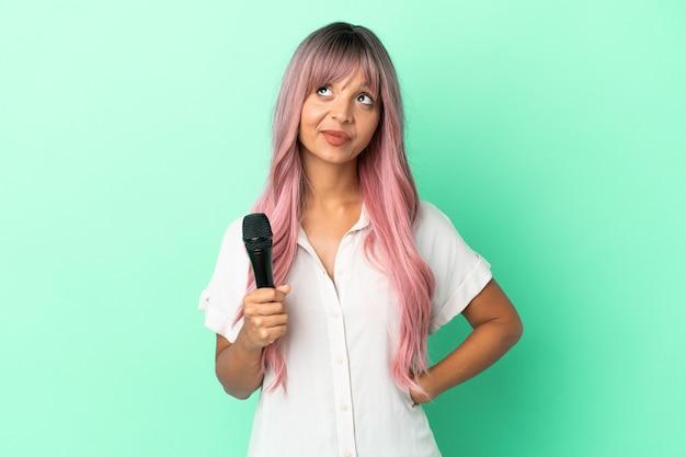 Молодая певица смешанной расы с розовыми волосами изолирована на зеленом фоне и смотрит вверх
