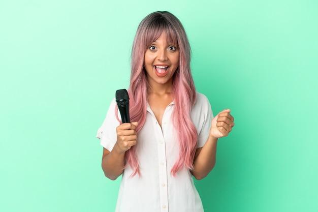 Молодая певица смешанной расы с розовыми волосами, изолированными на зеленом фоне, празднует победу в позиции победителя