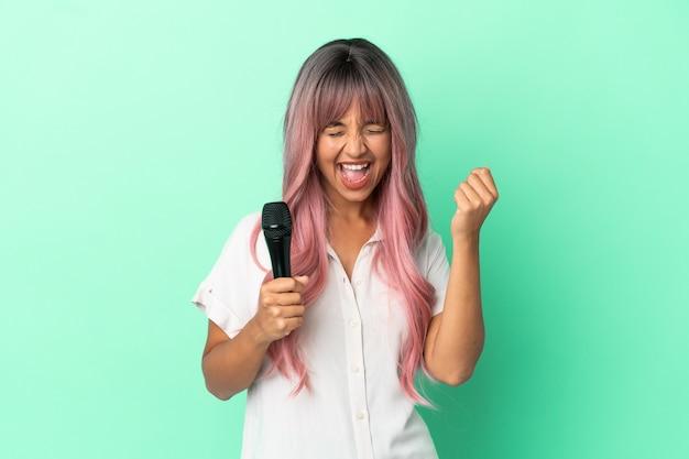 Молодая певица смешанной расы с розовыми волосами, изолированными на зеленом фоне, празднует победу