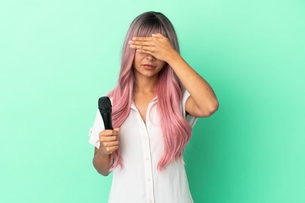 Молодая женщина певицы смешанной расы с розовыми волосами, изолированными на зеленом фоне, закрывая глаза руками. не хочу что-то видеть