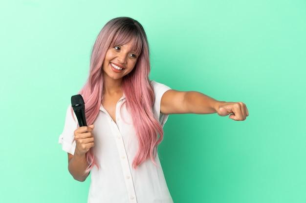 Молодая певица смешанной расы с розовыми волосами, изолированными на зеленом фоне, показывает палец вверх