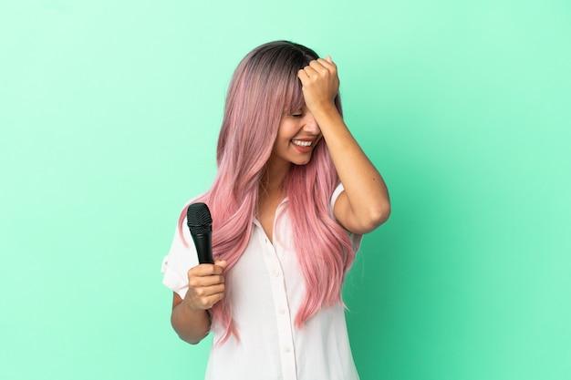 Молодая певица смешанной расы с розовыми волосами, изолированными на зеленом фоне, кое-что поняла и намеревается решить