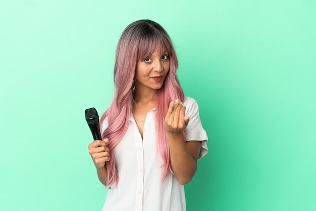 Молодая женщина певицы смешанной расы с розовыми волосами, изолированными на зеленом фоне, приглашая прийти с рукой. счастлив что ты пришел